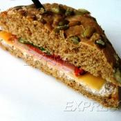 Сэндвич из зернового панини с сливочным сыром, ветчиной, сыром Эдем и помидорчиком